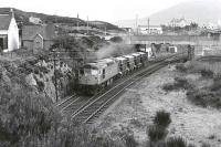 26013 departs Kyle with Presflos for the Howard Doris oil rig yard at Stromeferry in 1977.  The former locomotive shed was located on the right.<br><br>[Bill Roberton&nbsp;//1977]
