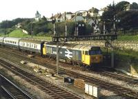English Electric Class 50 No. 50022 <I>Anson</I> draws forward under an impressive lower quadrant signal gantry at the west end of Newton Abbot in the summer of 1986. The train is an evening service from the Plymouth line and heading for Paddington. <I>Anson</I> was withdrawn in September 1988 and cut up at Vic Berry's yard in Leicester the following year.<br><br>[Mark Bartlett&nbsp;/07/1986]