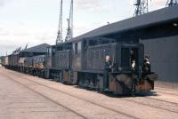 Labour-intensive shunting operations at Leith Docks in 1961 as North British Locomotive Company 0-4-0 diesel hydraulics D2731 and D2724 (successors to the steam J88s) haul a mixed freight eastwards towards Leith South yard.<br><br>[Frank Spaven Collection (Courtesy David Spaven)&nbsp;26/08/1961]