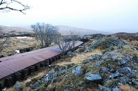 View south over the southern half of the Cruach Rock Snowshed. This is a covered cutting running north 205 yards from a girder overbridge. The roof is made of corrugated iron laid over a structure built of old rails with two walls built on either side of the cutting. There is a central portion which can be lifted off in the summer and replaced to keep the snow out of the cutting. When a train passes some of the central portions are lifted by the dam of air pushed by the train. Spoil from the cutting can be seen on the right.<br><br>[Ewan Crawford&nbsp;15/02/2010]
