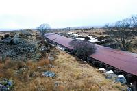 View north over the northern half of the Cruach Rock Snowshed. This is a covered cutting running north 205 yards from a girder overbridge. The roof is made of corrugated iron laid over a structure built of old rails with two walls built on either side of the cutting. There is a central portion which can be lifted off in the summer and replaced to keep the snow out of the cutting. When a train passes some of the central portions are lifted by the dam of air pushed by the train. Spoil from the cutting can be seen on the left.<br><br>[Ewan Crawford&nbsp;15/02/2010]