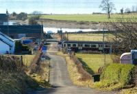 Looking south along the unclassified road at Ardmore Point towards the River Clyde on 1 March 2010. The barriers are down at Ardmore East level crossing as a Glasgow bound Class 320 passes.<br><br>[John McIntyre&nbsp;01/03/2010]
