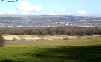 A panoramic shot looking east over the town of Horwich on a chilly 2 March 2010, with the appropriately named Winter Hill in the background. The former railway works stretches across the centre of the frame as the top of a First TransPennine train is seen running past in the foreground on the line from Bolton to Chorley and Preston. Opened by the L&Y in 1886 the works employed over 5,000 people at it's peak. Horwich produced its last new locomotive in 1957 and completed its last overhaul in 1964. The works continued to be used for general rolling stock into the 1980s but was eventually sold by BREL in 1988. The former works is now part of a large industrial estate named 'Horwich Loco' with most of the buildings still being put to good use.<br> <br><br>[John McIntyre&nbsp;02/03/2010]