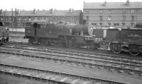 With the city of Nottingham's terraces forming the backdrop, Stanier 2-6-2T no 40165 stands alongside a converted tender in use as a sludge carrier at 16A's water softening plant. The photograph is thought to have been taken around 1961, the year the locomotive was withdrawn from nearby Kirkby in Ashfield shed.<br><br>[K A Gray&nbsp;//1961]