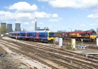 Scene at Didcot on 8 April 2010 as a Paddington bound First Great Western 165 DMU coming off the Oxford line passes 66024 on a freight.<br><br>[Peter Todd 08/04/2010]