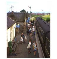 Not long before its 1965 closure, passengers (including the photographer's family in the foreground) wait to board an afternoon St Andrews - Edinburgh train at Crail's neat station and crossing loop on the single-track Fife Coast line. Latterly Crail had just four passenger trains a day, but one was a through service from Glasgow Buchanan Street, reflecting the traditional holiday attraction of the 'East Neuk' for Glaswegians. The original station building was subsequently incorporated within a garden centre on the site. [See image 4505] <br><br>[Frank Spaven Collection (Courtesy David Spaven)&nbsp;//1965]