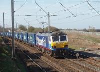 The pantograph on Stobart liveried 92017 is rising as it approaches Hest Bank level crossing where the wires are set high to provide clearance. The very long train was composed almost entirely of Tesco containers, with just a few empty flats at the rear, demonstrating DB's confidence in the Class 92 Co-Co electric's hauling capabilities over the climbs ahead. <br><br>[Mark Bartlett&nbsp;14/04/2010]