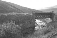 Approaching Inches station heading west towards Muirkirk in October 1964 with the Kennox Colliery branch coming in from the left and crossing the Douglas Water.  The bridge still survives but the railway is now a road at this point and no trace of Inches Station remains [See image 9066].<br> <br><br>[Colin Miller&nbsp;/10/1964]