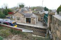 View north over the platforms and main station building at Polmont on 23 April 2010 as a 'non-stop' runs through westbound with an Edinburgh Waverley - Glasgow Queen Street service.<br><br>[John Furnevel&nbsp;23/04/2010]