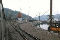 Eastern approach to Stromeferry in 1975, with a Howard Doris shunter [see image 28421] in the distance. The yard is a hive of activity with rail and sea freight, much of it destined for the HD oil platform construction yard at Loch Kishorn.<br><br>[Frank Spaven Collection (Courtesy David Spaven)&nbsp;//1975]