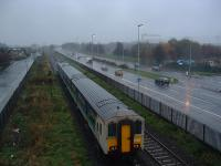 An ex-Bangor Belfast-bound DMU leaves Sydenham in 2003. A Harland and Wolff crane is just visible through the rain.<br><br>[Ewan Crawford&nbsp;17/11/2003]
