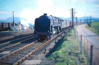 View south from the down platform at Symington in April 1959, with BR Light Pacific 72005 <I>Clan MacGregor</I> about to run through the station at the head of a down express. The train is passing the goods yard at the south end of the station with the former Caledonian Railway Peebles branch turning east on the other side (by this time having been cut back to Broughton). The road entrance on the right leads to a junction with the A702.<br><br>[A Snapper (Courtesy Bruce McCartney)&nbsp;04/04/1959]