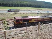 DBS 66106 waits alongside the M74 in the northbound loop at Beattock Summit for a Pendolino to overtake. The loco was hauling a lengthy train of bogie tankers. <br><br>[Mark Bartlett 18/05/2010]