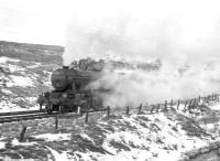 Gresley V2 2-6-2 no 60824 has just emerged from the south portal of Whitrope Tunnel with the 8.16am Millerhill - Carlisle freight (honest) on a wintery 30 December 1964. The train is about to pass the summit as it heads south towards Riccarton Junction. <br><br>[Robin Barbour Collection (Courtesy Bruce McCartney)&nbsp;30/12/1964]