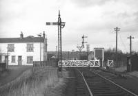 Glasgow Road level crossing in Bathgate in February 1970 [see image 29152] looking north west towards Bathgate Lower station. The sign on the building to the left on the other side of the crossing indicates use by the local Civil Defence Corps, stood down in the UK in 1968.<br><br>[Bill Jamieson&nbsp;/02/1970]