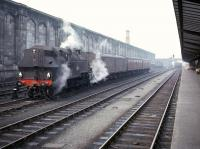 A quiet period at Carlisle station in the mid 1960s as Ivatt 2-6-2 tank no 41264 takes a break from shunting parcels vans to replenish its tanks from a hose in the west sidings. The locomotive spent the final period of its working life at Upperby after arriving there from Bradford (Low Moor) shed in 1965. <br><br>[Robin Barbour Collection (Courtesy Bruce McCartney)&nbsp;//]