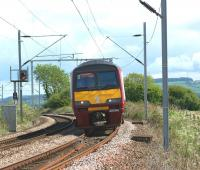 320318 approaches Brooks Farm LC between Cardross and Ardmore with a service to Helensburgh Central on 28 May 2010. The photo can be compared with one which was taken from the same spot some 37 years earlier [see image 18525]. The distant signal in the earlier shot was replaced during the Yoker area resignalling and the present signal is approximately 30 yards further east.<br> <br><br>[John McIntyre&nbsp;28/05/2010]