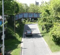 Photograph taken on June 2010 looking south west along the trackbed of the Caledonian a mile out of Princes Street, shortly after passing the site of Dalry Junction. The footbridge that spanned the tracks here still survives although nowadays it carries pedestrians between Dundee Terrace (left) and Dundee Street over what is now an exit from Edinburgh's Western Approach Road. Merchiston station lay straight ahead just beyond and to the left of St Michael's Parish Church on Slateford Road, the tower of which stands in the background.<br> <br><br>[John Furnevel&nbsp;03/06/2010]