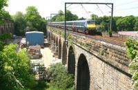 The 1247 'East Coast' Glasgow Central - Kings Cross train crossing Slateford Viaduct on 3 June 2010, some two miles short of its next scheduled stop at Haymarket. The substantial parallel structure on the far left of the photograph is the aqueduct carrying the Union Canal.<br><br>[John Furnevel&nbsp;03/06/2010]