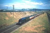 One of Haymarket's finest, no 60011 <I>'Empire of India'</I>, sweeps through Musselburgh on 16 July 1955 carrying the headboard of the down <I>Flying Scotsman</I>. On the right the freight lines from Monktonhall Junction climb towards the camera.<br><br>[A Snapper (Courtesy Bruce McCartney)&nbsp;16/07/1955]