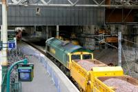 Scene during the major works at Waverley in 2006 as Freightliner 66607 creeps into the former platform 1 at the east end of the station with a ballast train. Note the access road created on the right for plant and materials coming in from Calton Road with a transporter/lifting unit in the process of leaving the station.<br><br>[John Furnevel&nbsp;/02/2006]