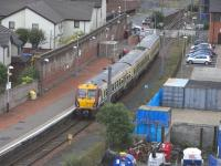Ardrossan Town station, photographed from the Castle Hill on 14 June 2010 with 334 039 about to leave on the short (but slow) hop to Ardrossan Harbour.� Road traffic on Princes Street has already been stopped. This was once a more substantial station with two through lines and two bays and a street-fronting building to the right.� Remains of the original structure were still obvious when the station reopened in 1987 as a single platform, but all has now gone.�Happily though the platform is being extended at the eastern end (off camera).<br> <br><br>[David Panton&nbsp;14/06/2010]