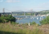 Brunel's famous Saltash suspension bridge over the Tamar estuary (or as it is technically known - lenticular truss viaduct), as seen from an approaching Penzance to Exeter train, which is just about to call at Saltash station and then swing sharply right onto the bridge approach. Under the left hand span the Ernsettle Royal Navy depot, rail served from the Gunnislake branch that runs along the far shore, can be seen.  <br><br>[Mark Bartlett&nbsp;15/06/2010]