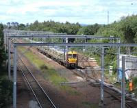 A track worker acknowledges the hootings of an incoming Ayrshire service passing Cardonald Junction on 16 June with the branch to Deanside Transit running off to the right.<br><br>[David Panton&nbsp;16/06/2010]