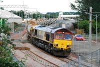 66162 slowly passes over the level crossing located to the east of the former Bathgate Upper station. The new station can be seen in the background. This ballast train halted after crossing to await instructions.<br><br>[Ewan Crawford&nbsp;27/06/2010]