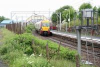 The 1340 Helensburgh Central - Airdrie service (334009)  arrives at Craigendoran at 1343 on a rainy 8 June 2010. The photograph is taken from the trackbed of the line that once branched left here onto the pier platform. The path straight ahead leads to the footbridge and the exit to Station Road beyond the car park. <br><br>[John Furnevel&nbsp;08/06/2010]