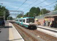 The new junction for the Didsbury line can be seen immediately behind this Altrincham to Bury tram arriving at Trafford Bar. To maintain capacity however a <I>diveunder</I> has been created for Manchester bound trams rather than a plain junction. Being able to use the old MSJA OLE gantries must have saved a fortune when this line was converted to Metrolink in 1992.<br><br>[Mark Bartlett&nbsp;30/06/2010]