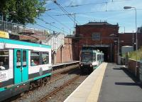 Trafford Bar was the original Old Trafford station, the name change only coming about in 1992 when Warwick Road, outside the cricket ground, was renamed Old Trafford. The original station booking hall still stands above the short tunnel. Two Altrincham services are seen passing here and the station, which enjoys a six minute frequency service, will become even busier when the Didsbury line opens. <br><br>[Mark Bartlett&nbsp;30/06/2010]