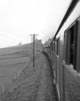 View from a train window as A3 Pacific no 4472 <I>Flying Scotsman</I> heads north towards Perth on the Kinross-shire line with the Queen's College Railway and Transport Society's <I>Flying Scotsman Rail Tour</I> on 16 May 1964. [See image 24811]. The photograph is thought to have been taken about a mile north of Kelty.<br><br>[Robin Barbour Collection (Courtesy Bruce McCartney)&nbsp;16/05/1964]