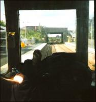 First generaton DMUs allowed you the simple pleasure of 'playing <br> driver', provided the driver hadn't been a spoilsport and pulled down the blind behind him (admittedly necessary at night to prevent <br> distracting reflections).� It's September 1999 and there are just a <br> couple of months left of Class 117s operating out of Edinburgh from <br> where, for a few years, they'd been used only at peak times.� With the driver's hand (and paper) in view, and watched by a figure on the bridge, the unit comes to a halt at Rosyth with a northbound service. <br> <br><br>[David Panton&nbsp;/09/1999]
