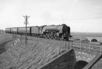 A1 Pacific no 60147 <I>North Eastern</I> approaching Innerwick in April 1964 with the 3.48pm (SO) Edinburgh - Berwick stopping train. The old A1 can be seen crossing Dryburn Bridge beyond the train and Barns Ness lighthouse stands in the background. [With thanks to Bill Jamieson] <br><br>[Robin Barbour Collection (Courtesy Bruce McCartney)&nbsp;/04/1964]