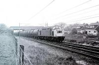 An unidentified Class 40 hustles a train of oil tanks along the Up Slow line through the site of Balshaw Lane & Euxton station, which had closed in 1969 and been cleared away for the 1972 electrification. By 1998 a new (and renamed) station had opened at this location. [See image 29818] for a Then and Now comparison that illustrates the positive developments at this site.<br><br>[Mark Bartlett&nbsp;//1981]