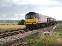 In 2010, before the <I>Super 60</I> refurbishment programme, there were still a few Class 60s working hard on the mainline and here 60040 <I>The Territorial Army Centenary</I>, in <I>Army</I> livery, heads a lengthy oil train north at Tredington level crossing between Cheltenham and Aschurch.<br><br>[Mark Bartlett&nbsp;17/07/2010]