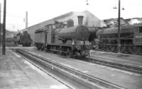 Shed scene at Trafford Park (9E), Manchester, on 21 June 1958, with class J10 no 65166 centre stage and Black 5 no 45239 standing on the right. Trafford Park closed to steam in 1968 and the shed was demolished in the mid 1970s. A large Freightliner depot was later built on the site. <br> <br><br>[Robin Barbour Collection (Courtesy Bruce McCartney)&nbsp;21/06/1958]