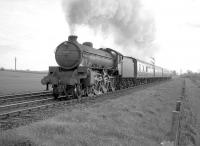 B1 no 61029 <I>Chamois</I> with an up train on the ECML west of Prestonpans in April 1964. (The train is possibly the Dunbar local that left Waverley around 5.38pm and Prestonpans at 6.01pm.) Dolphingstone LC is behind the train and Morrisons Haven SB can be seen in the right background. Major realignment of the ECML was carried out in this area some 40 years later due to subsidence resulting from old mine workings [see image 24240].<br><br>[Robin Barbour Collection (Courtesy Bruce McCartney)&nbsp;22/04/1964]