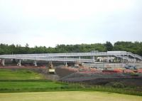 Mega footbridge structure at the new Blackridge Station site viewed from the A89 on 23 June, with the rail trolley of the tracklaying train having run to the rear of the unit in the station area to collect further supplies of sleepers. <br><br>[David Pesterfield 23/06/2010]