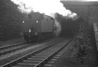 The back end of hard-working Austerity 2-8-0 no 90434 is about to disappear into the smoke-filled tunnel at the west end of Beamish station in the winter of 1964. In front of the locomotive is iron ore bound for the blast furnaces at Consett, with BR Standard class 9F 2-10-0 no 92097 working just as hard at the other end. Conditions on the footplate inside the tunnel must have been grim.   <br><br>[K A Gray&nbsp;15/02/1964]