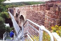 <I>'After you dear...'</I> Tentatively trying out the pedestrian footbridge (completed 1999) alongside the Oykel Viaduct on the walk from Culrain to Invershin in September 2001. The metal footbridge is bolted onto the west side of the viaduct.<br><br>[John Furnevel&nbsp;14/09/2001]