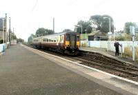 Platform scene at Kirknewton in September 2002. The driver of an Edinburgh - Glasgow Central stopping train is manually activating the half-barrier level crossing before leaving the station.<br><br>[John Furnevel&nbsp;03/09/2002]