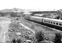 A Glasgow - Leeds train shortly after restarting from Dumfries in 1982, passing the site of Dumfries shed, with the buildings now demolished. This view from St Mary's Street bridge had not been possible prior to demolition of the old shed.<br><br>[John Furnevel&nbsp;18/06/1982]