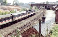 A dead electric train is dragged south through Dumfries by a class 47 on a Sunday morning in June 1991, with locomotive and stock in immaculate BR InterCity livery. The train is passing preparatory works for the new Dumfries & Galloway police HQ on the site once occupied by Dumfries shed.<br><br>[John Furnevel&nbsp;23/06/1991]