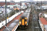 Looking east from the station footbridge at Slateford on 29 December 2004 as a morning Glasgow Central - Edinburgh Waverley service pulls away from the platform. At this point the train is running alongside city bound traffic on Slateford Road.<br><br>[John Furnevel&nbsp;29/12/2004]