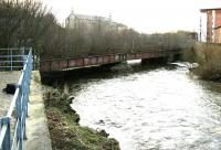 Looking west over the River Kelvin in February 2005 from the car park of Glasgow Museum of Transport off Bunhouse Road. The photograph shows the girder viaduct that once carried the Glasgow Central Railway across the River towards Partick Central station, whose former main entrance and booking office can be seen standing on Benalder Street in the right background.<br><br>[John Furnevel&nbsp;19/02/2005]