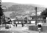 Looking west along the A811 Balloch Road on 28 June 1971 as a class AM3 electric leaves Balloch Central station via the level crossing on a service to Airdrie.<br><br>[John Furnevel&nbsp;28/06/1971]