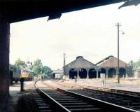 The shell of Dumfries shed on a quiet Sunday in June 1969. View north through Annan Road Bridge with the station in the background. The type 2 diesel stabled alongside the old goods depot is probably diagrammed for the first ICI working from Cargenbridge on Monday morning.<br><br>[John Furnevel&nbsp;22/06/1969]