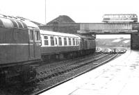 A downpour at Dumfries in 1972 as an EE Type 4 leaves the station with a train for the south passing 5378 standing on the centre road. The roof of the former Dumfries locomotive shed, closed approximately 7 years earlier, is visible just beyond St Mary's Street Bridge. <br><br>[John Furnevel&nbsp;28/05/1972]